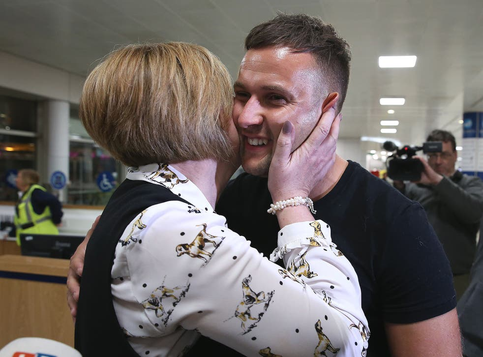 Jamie Harron, who was sentenced to three months in a Dubai jail for touching a man's hip, with his mother Patricia after arriving at Glasgow Airport