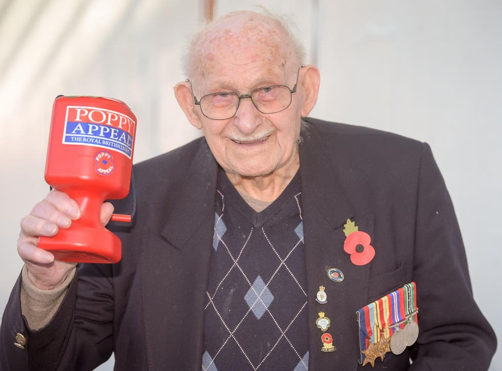 Poppy seller Ron Jones, who is 100 years old, holds his collection box outside a Tesco supermarket in Newport