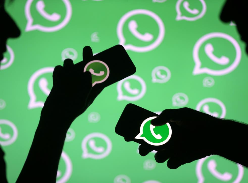 Men pose with smartphones in front of displayed Whatsapp logo in this illustration September 14, 2017