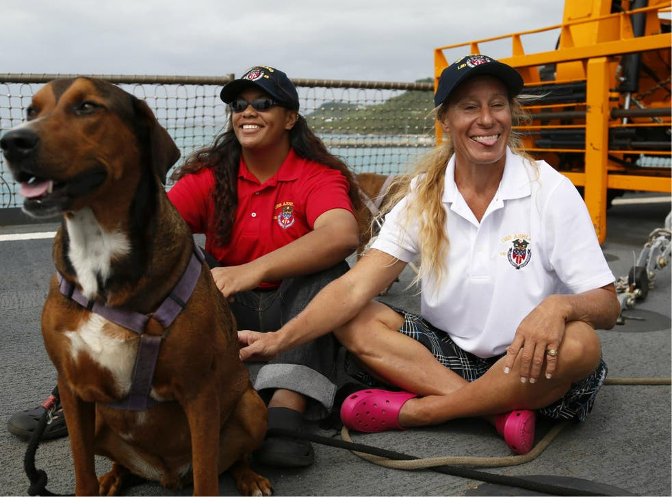 Jennifer Appel, right, and Tasha Fuiava sit with their dogs on the deck of the USS Ashland Monday, 30 October 2017 in Okinawa, Japan.