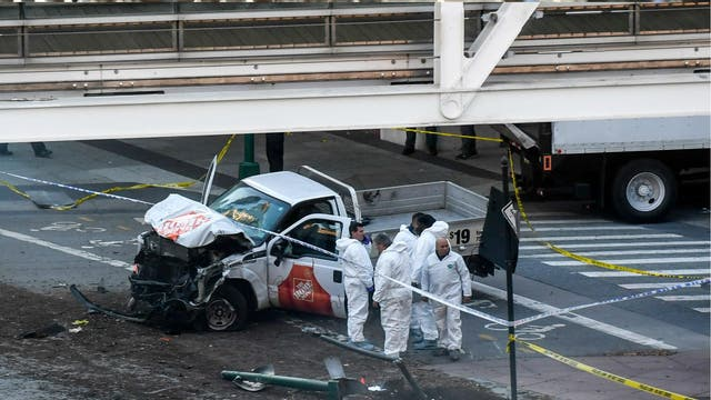 Investigators inspect a truck following a shooting incident in New York on 31 October 2017. Several people were killed and numerous others injured in New York on Tuesday when a suspect plowed a vehicle into a bike and pedestrian path in Lower Manhattan, and struck another vehicle on Halloween, police said. A suspect exited the vehicle holding up fake guns, before being shot by police and taken into custody, officers said. The motive was not immediately apparent.