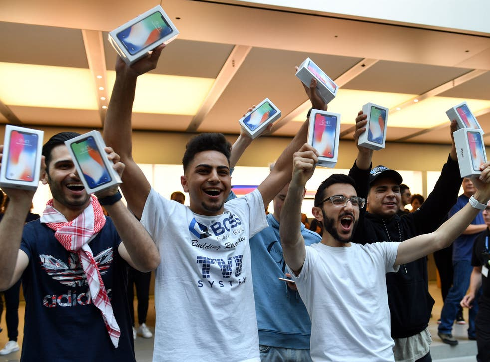 The first customers at an Apple showroom in Sydney display their iPhone X purchases