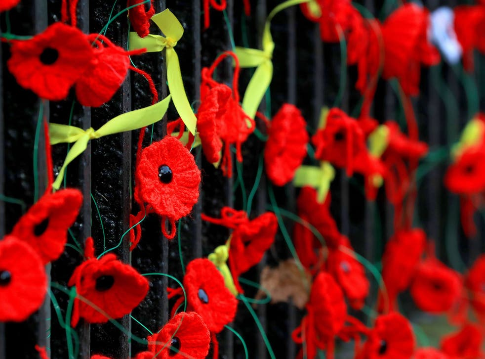 Knitted poppies and yellow ribbons placed outside Holy Trinity Church in Wavertree, Liverpool