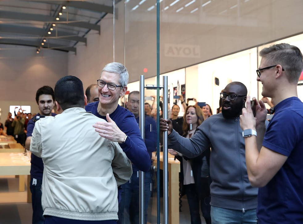 Apple CEO Tim Cook greets customers as they queue to buy new iPhone X