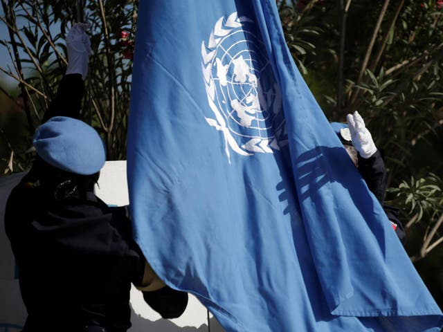 Senegalese officers raise a United Nations flag during the opening ceremony of the Mission for Justice support in Haiti