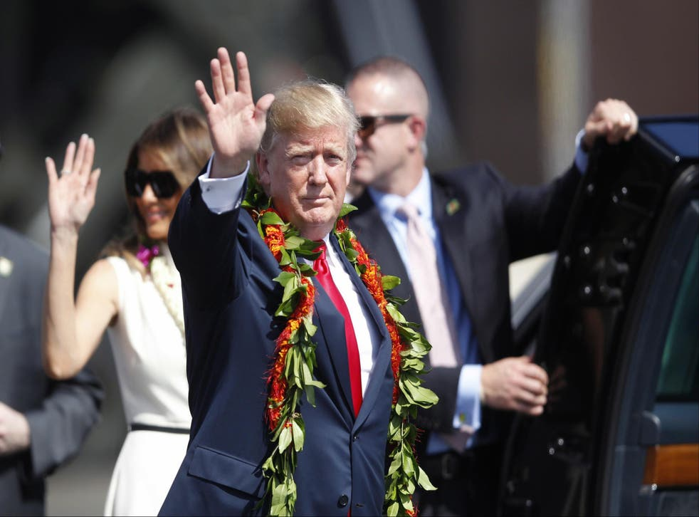 Adorned with lei, President Donald Trump walks towards the motorcade with first lady Melania Trump in Honolulu