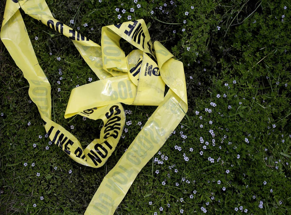 Yellow police crime scene tape rests in the grass in Baton Rouge, Louisiana after an unrelated crime