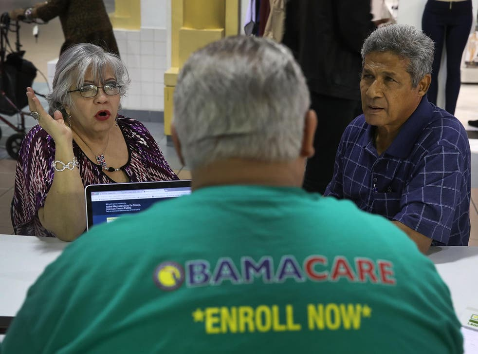 Isabel Diaz Tinoco and Jose Luis Tinoco speak with an insurance agent as they shop for insurance under the Affordable Care Act  in Miami, Florida.