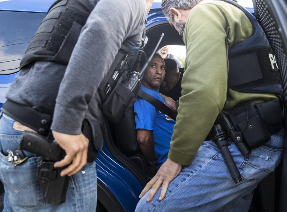 Immigration and Customs Enforcement agents take green card holder Sergio Rodriguez into custody outside his home El Monte, California, in June