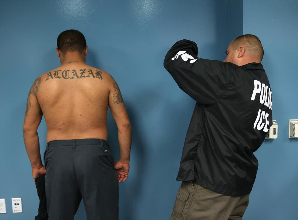 An ICE agent documents a detained individual