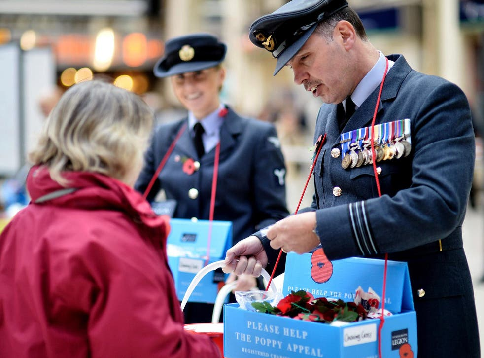Members of the armed forces sell poppies at London's Charing Cross station