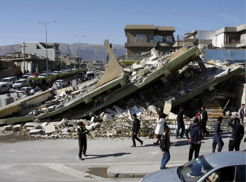 People gather around a levelled building in the mountainous town of Darbandikhan in Iraqi Kurdistan on 13 November 2017, following a 7.3-magnitude earthquake.