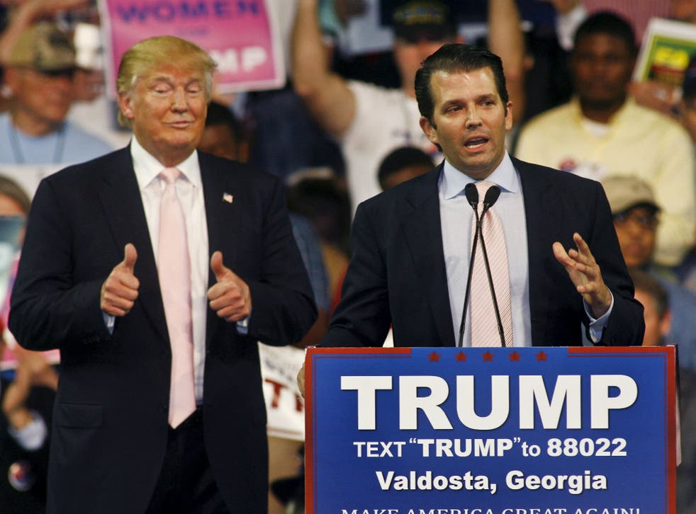 Donald Trump gives a thumbs up as his son Donald Trump, Jr. speaks at a campaign rally at Valdosta State University in Valdosta, Georgia February 29, 2016