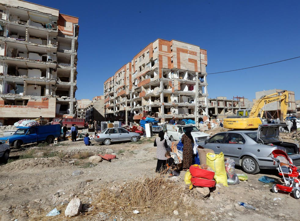 People collect belongings from damaged buildings in the city of Sarpol-e-Zahab in Kermanshah province