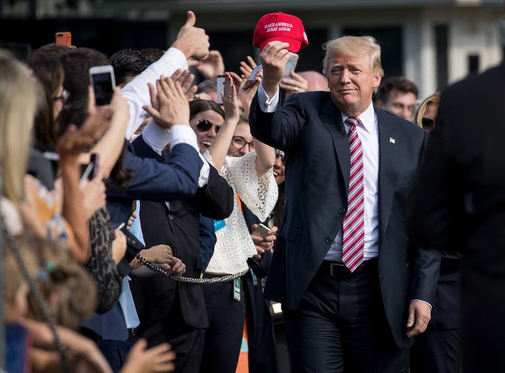 President Donald Trump holds up a 'Make America Great Again' hat