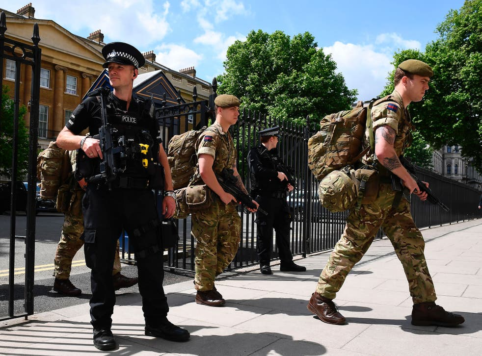 Ministry of Defence Police officers on guard as soldiers enter a building in central London on 24 May 2017