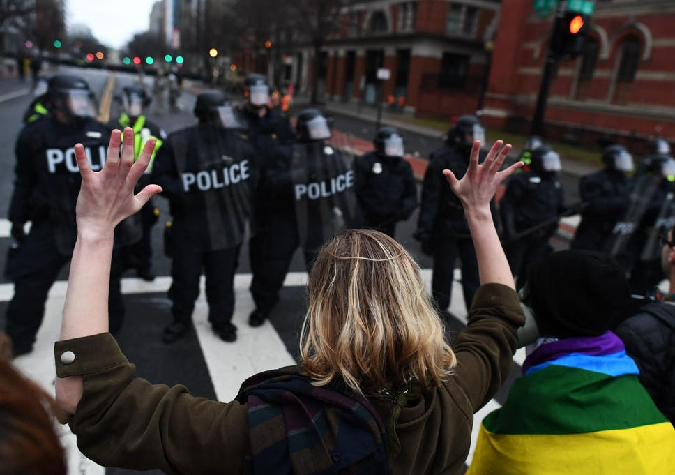 An anti-Trump protester holds her hands up as police officers lineup in  Washington ee2da9c38a22