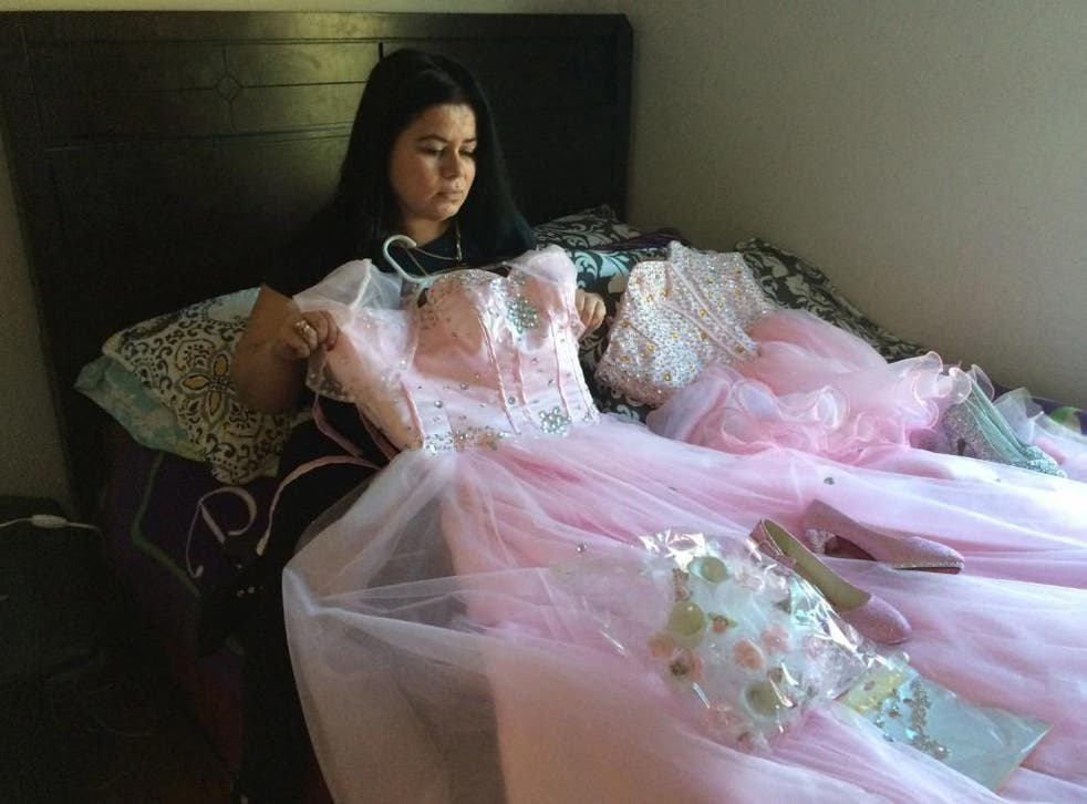 Maria Reyes holds a dress her daughter Damaris was going to wear for a Sweet 15 Quinceanera celebration