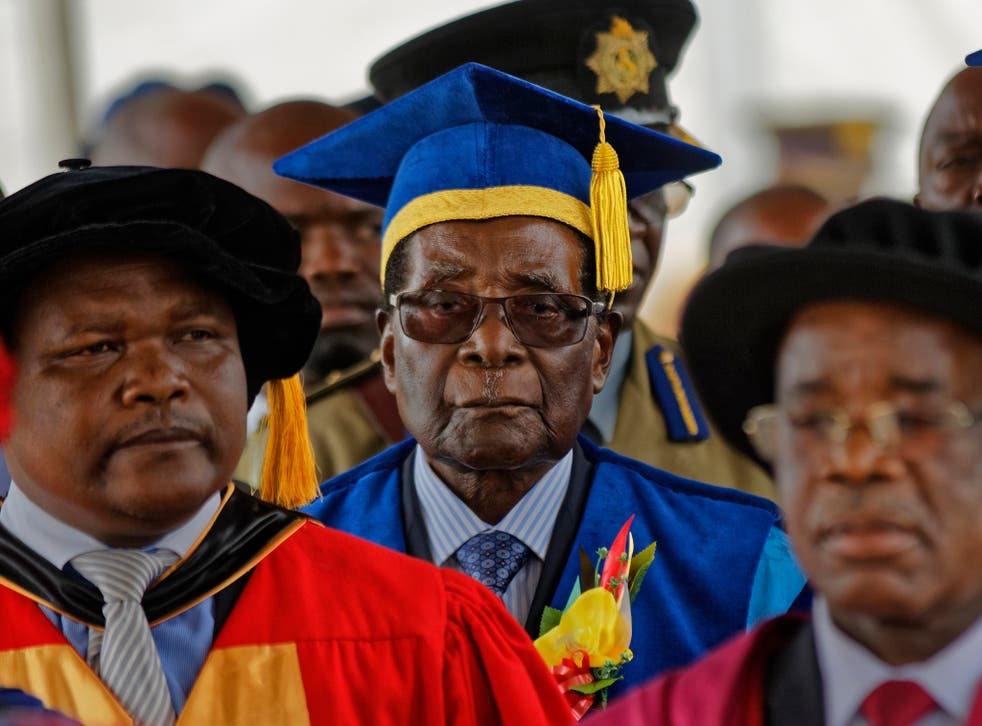 Robert Mugabe presides over a student graduation ceremony at Zimbabwe Open University yesterday, his first public appearance since the military put him under house arrest