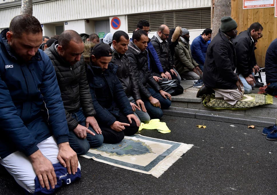 People pray in a street on 10 November  in Clichy, near Paris, while the city mayor demonstrate with others political leaders against Muslim streets prayers