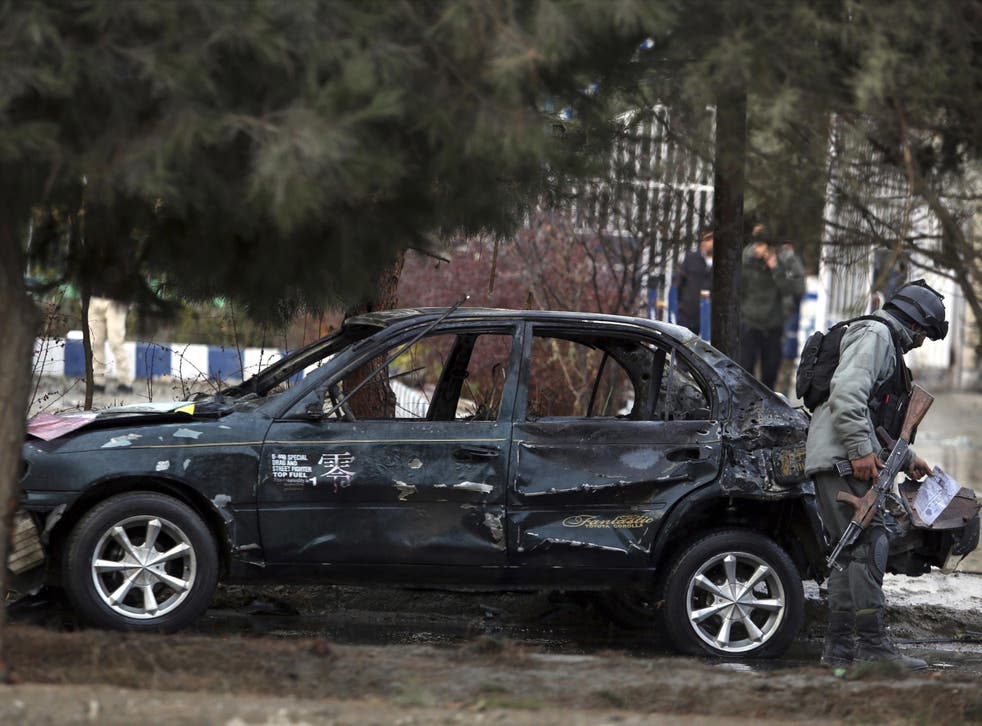 An Afghan security personnel inspects the site of a deadly suicide bombing in Kabul