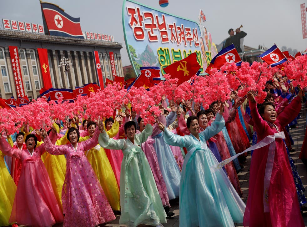Women wearing traditional clothes react as they march past the stand with North Korean leader Kim Jong-un during a military parade marking the 105th birth anniversary of the country's founding father, Kim Il-sung in Pyongyang