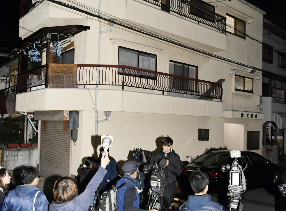 Press gather outside the apartment in Neyagawa, Osaka, where buckets filled with concrete and human bones were found