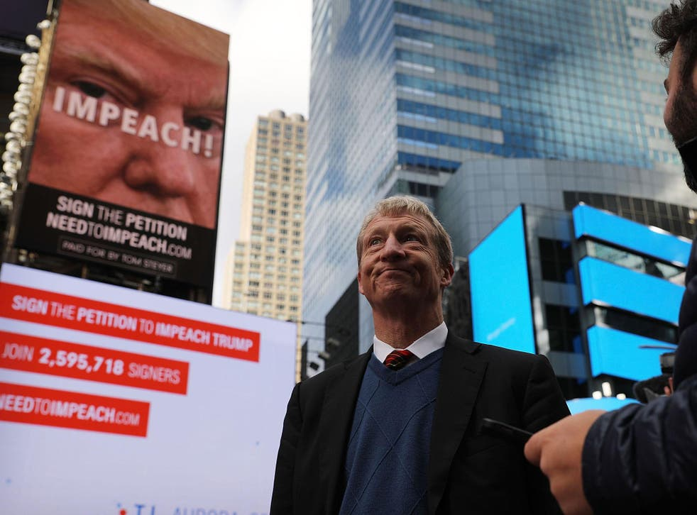 Tom Steyer stands in front of one of the billboards he has funded in Times Square calling for the impeachment of President Donald Trump