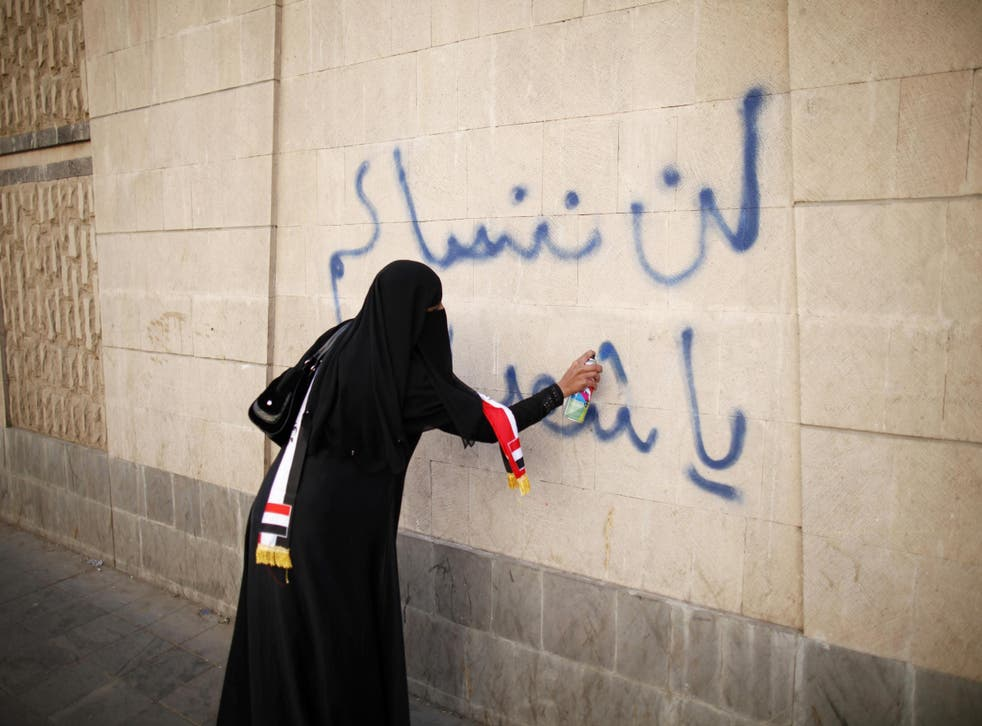 A woman writes 'We won't forget you, oh our martyrs' on a wall in Sanaa, Yemen during a 2013 protest demanding an end to the violence which consumed the country after the Arab Spring