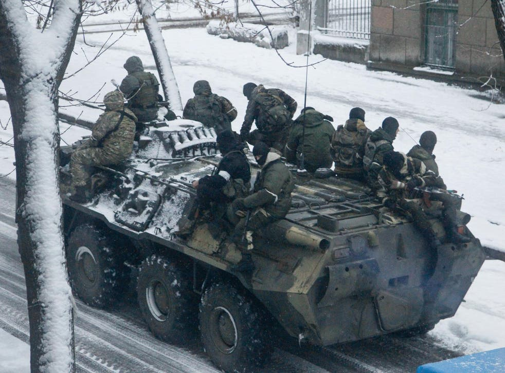 Armed men without insignia ride on a personnel carrier along a street in Luhansk city, Ukraine, on 23 November 2017