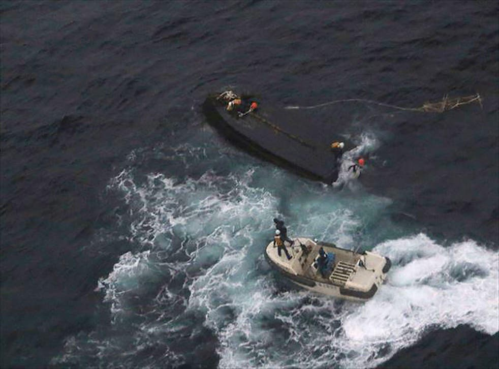 A Japanese Coast Guard rescue team approaching a capsized North Korean boat on the Sea of Japan about 225 miles north west of the Noto Peninsula in Ishikawa Prefecture