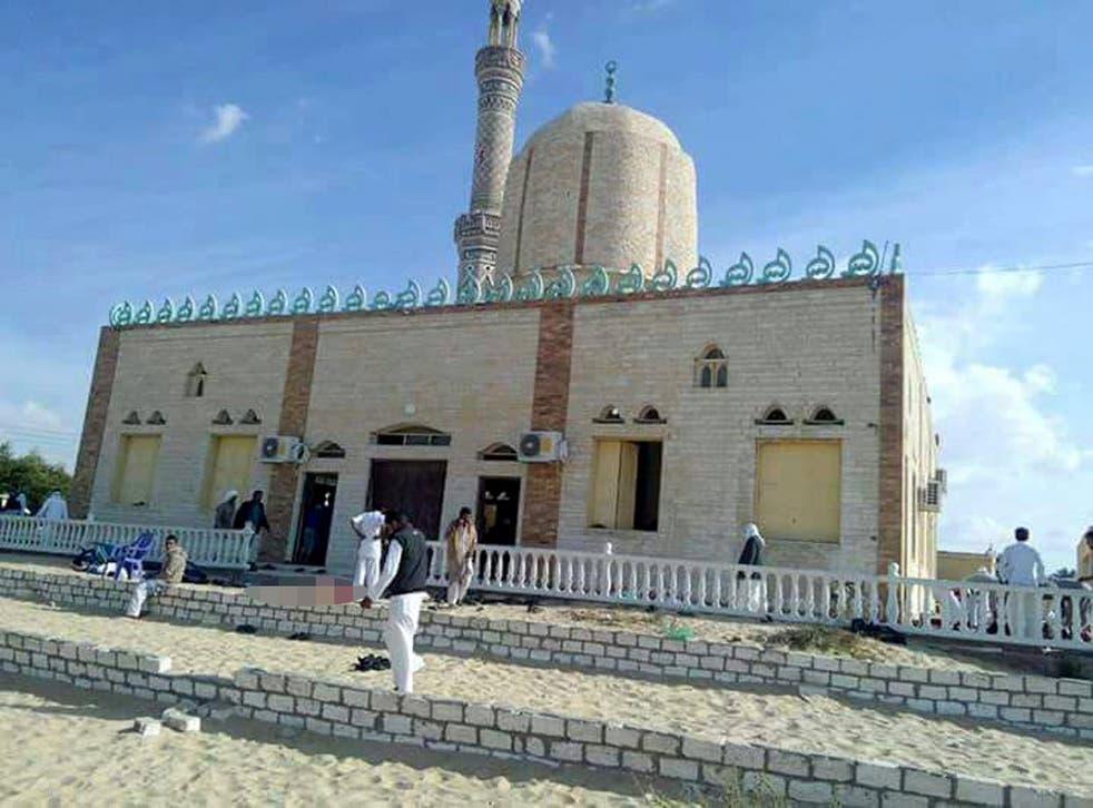 People walk outside a mosque that was attacked in the northern city of Arish, Sinai Peninsula