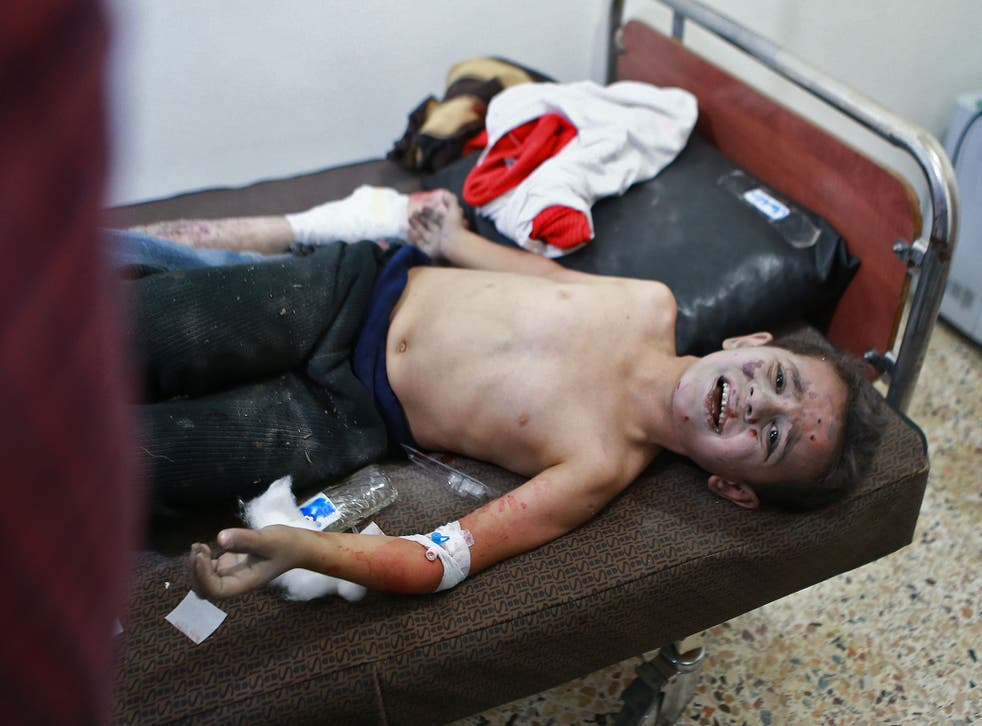 A Syrian boy receives treatment for his wounds in a hospital following a reported air strike in the rebel-held besieged town of Arbin