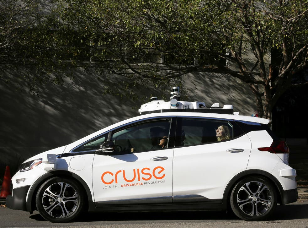 A woman smiles in the back seat of a self-driving Chevy Bolt EV car during a media event by Cruise, GM's autonomous car unit, in San Francisco on November 28, 2017