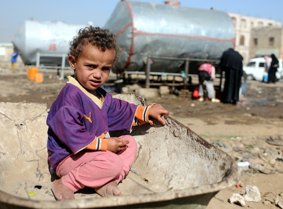 A Yemeni child sits on a wheelbarrow as he waits for his mother to fill their jerry cans with clean water