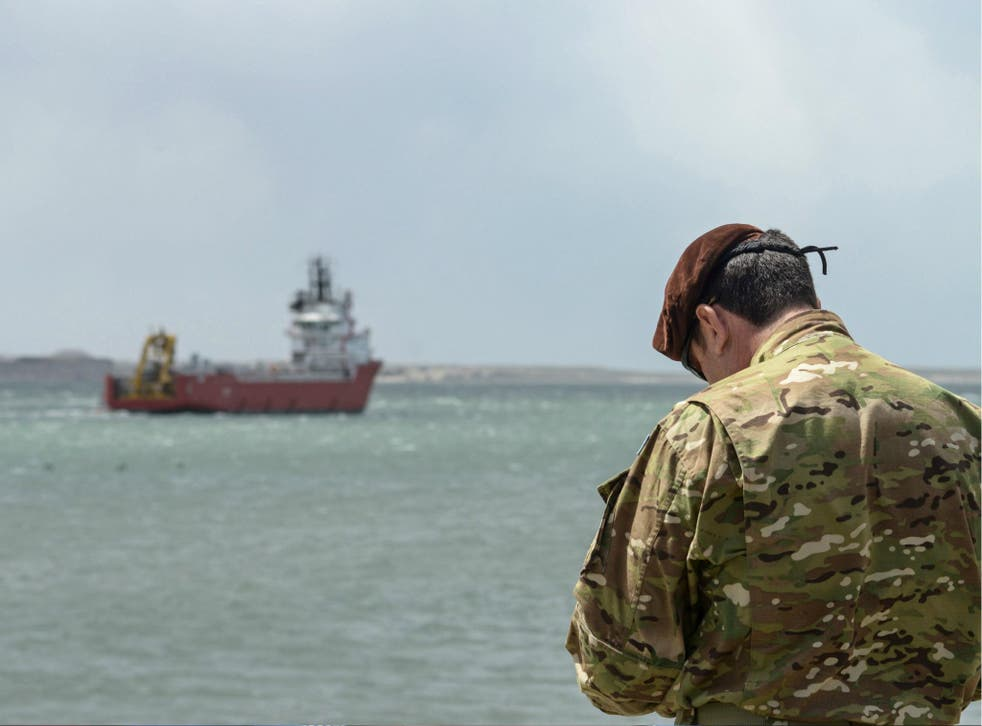 A member of the U.S. Navy stands at Comodoro Rivadavia harbour after the US Navy installed its deep diving rescue vehicle on the Sophie Siem vessel