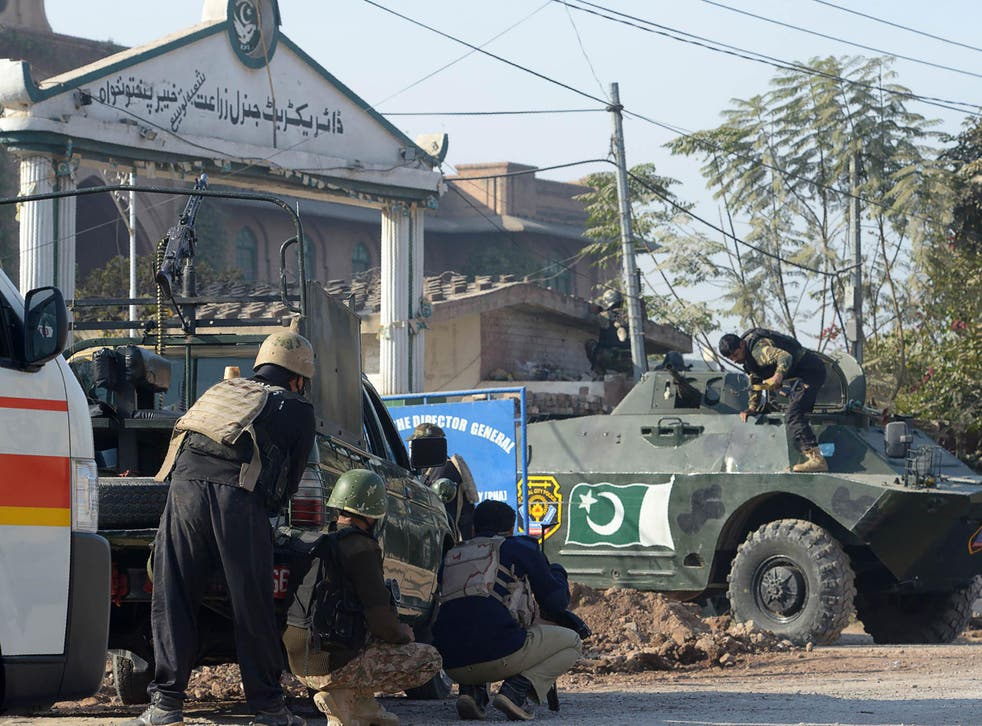 Pakistani security personnel take position outside an Agriculture Training Institute after an attack by Taliban militants in Peshawar