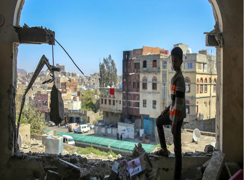 A Yemeni boy checks the damage following a mortar shell attack on the country's southern city of Taez
