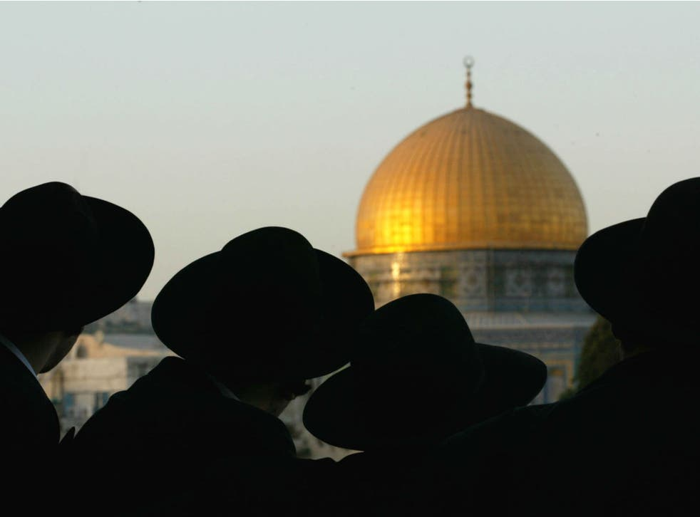 Ultra-Orthodox Jews look at the Dome of the Rock, one of the holiest sites for Muslims, in Jerusalem on August 8, 2002
