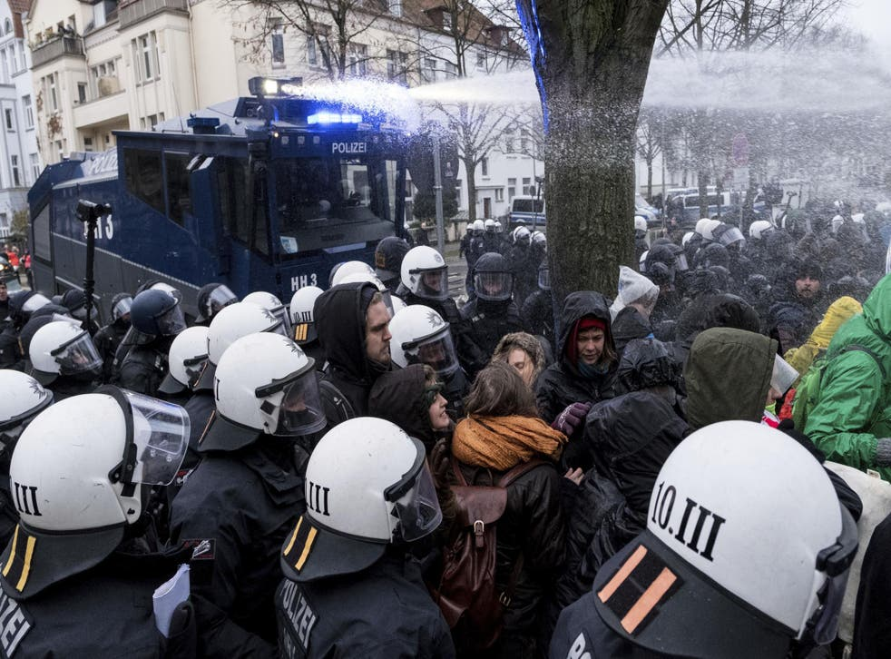 Police use a water cannon to clear a street blocked by demonstrators near the venue of the AfD convention in Hanover