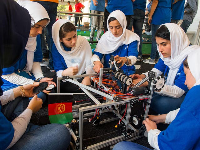 Members of the Afghan all-girls robotics team make adjustments to the team robot in the practice area on July 17, 2017