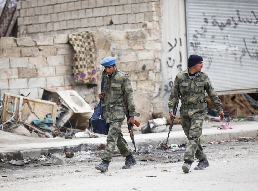Members of the Free Police walk along a street in al-Rai, Syria