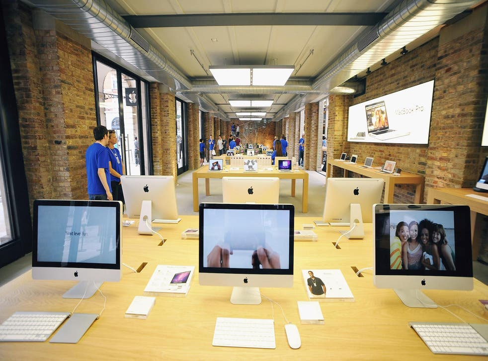 Tables of Apple Mac products on display in the Apple Store In Covent Garden