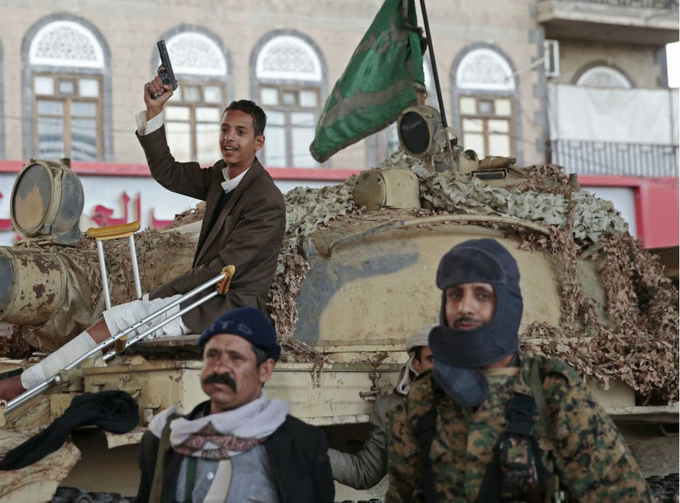 Houthi fighters guard a street leading to the residence of former Yemeni President Ali Abdullah Saleh