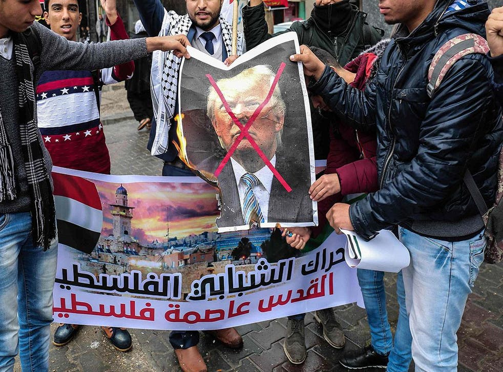 Palestinian protesters prepare to burn a picture of Donald Trump in the southern Gaza Strip town of Rafah