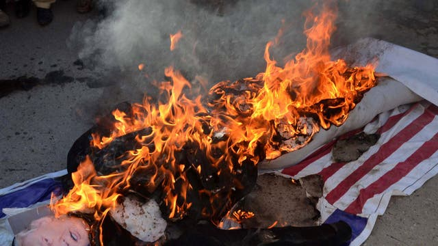 Supporters of Difa-e-Pakistan Council a coalition of right wing Islamic parties, burn an effigy of US President Donald Trump, during a protest in Quetta, Pakistan