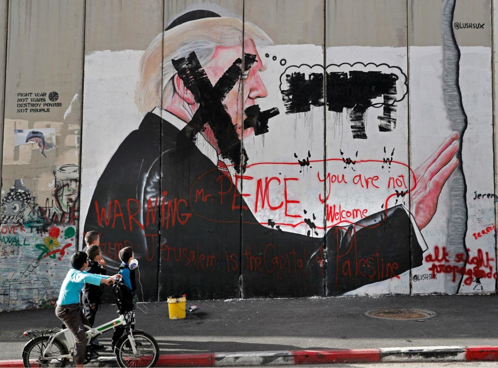 Vandalised graffiti depicting the US President is painted on Israel's controversial separation barrier in the West Bank city of Bethlehem