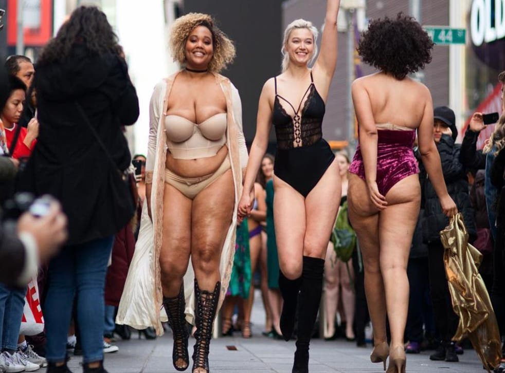 """Models hold hands during """"The Real Catwalk"""" fashion show in Times Square"""