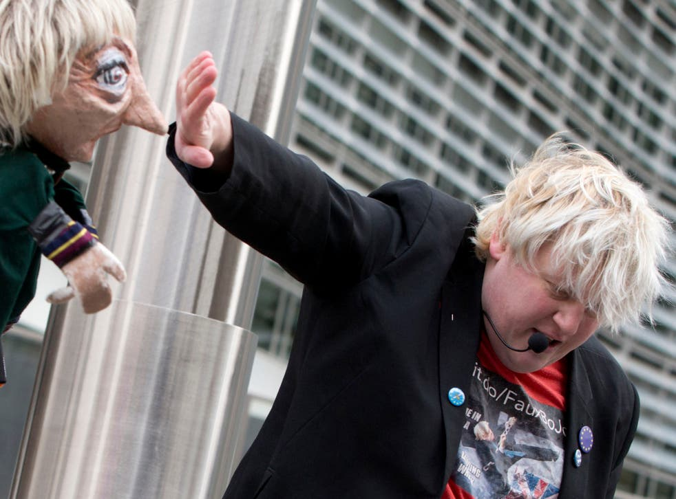 A man imitating Boris Johnson plays in a skit with a puppet of Theresa May outside EU headquarters in Brussels last week