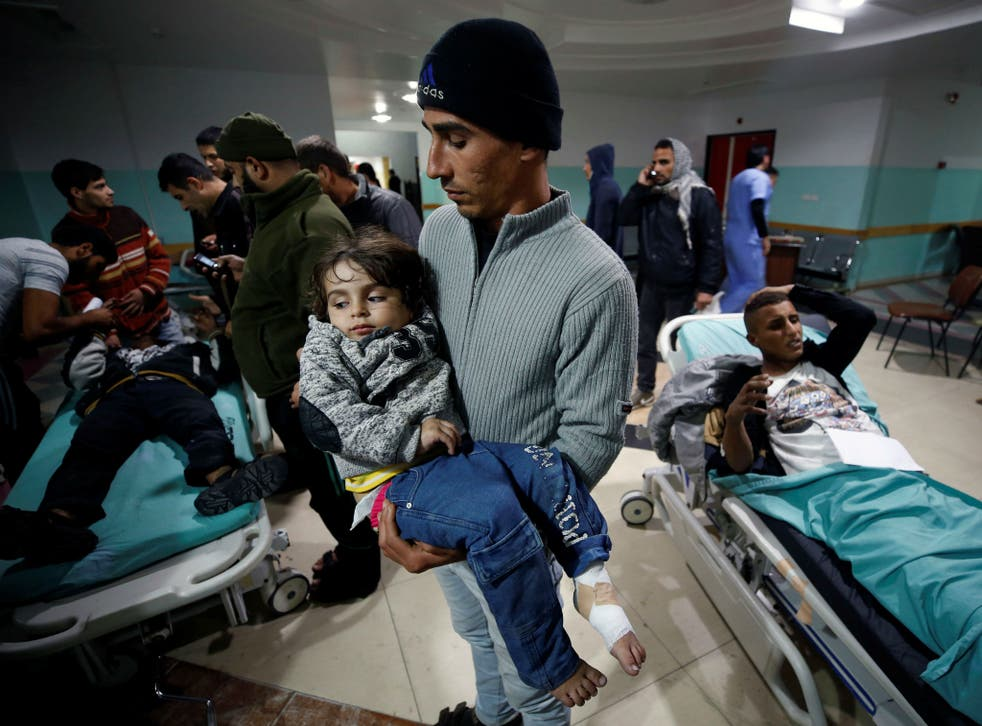 A Palestinian man carries his wounded daughter as she waits to receive treatment at a hospital near to the site of an Israeli air strike